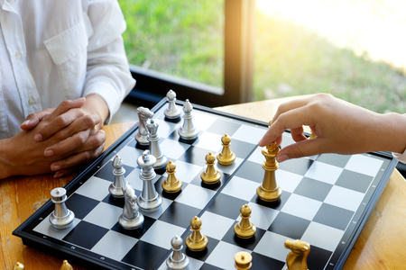 Two businesswoman thinking and hold king chess on her hand, on board of chess game silver and gold color chess are on the table
