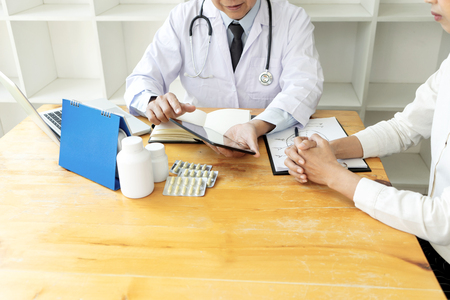 professional doctor sit at the table and talk about health care to the patient, on the table there are bottle of medicine. Stock Photo