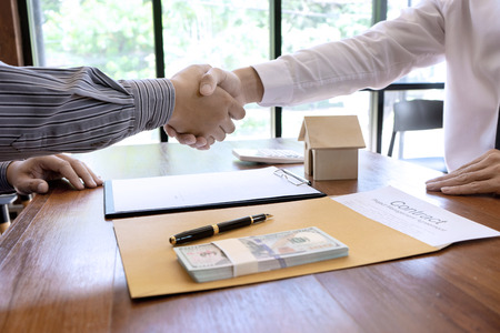 Business man agreement to sign for contract for new home buy or rent , talking and have a home model on the table Stock Photo - 124947063