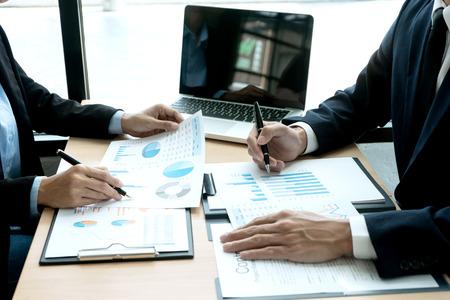 Equipo de jóvenes empresarios en una pequeña reunión en la oficina hablar sobre análisis gráfico plan de marketing gráfico con computadora portátil. Foto de archivo