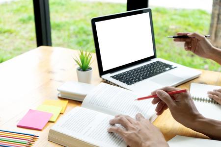 La mujer y el hombre trabajan en la mesa con el trabajo de papel de la computadora portátil y el bolígrafo de color, en concepto de educación o negocio, con pantalla de computadora blanca con trazado de recorte