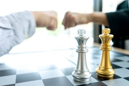 Businessman fist bump  near the chess board silver and gold color on the office desk.