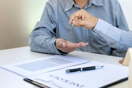 Business man agreement to sign for contract and get key for new home buy or rent