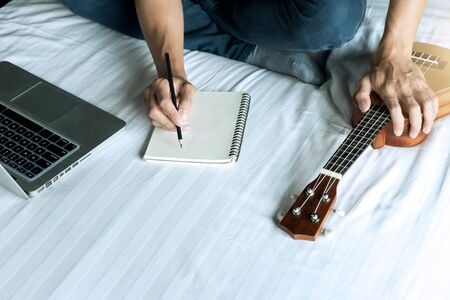 young man write a song or music with her Ukulele play Imagens
