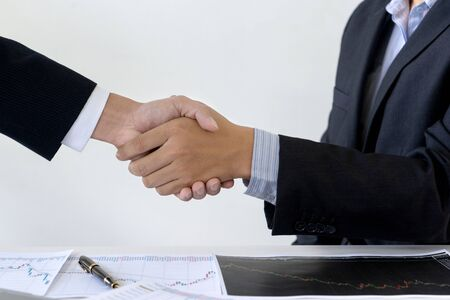businessman shake hand at the office table between computer laptop , success or agreement about their job.