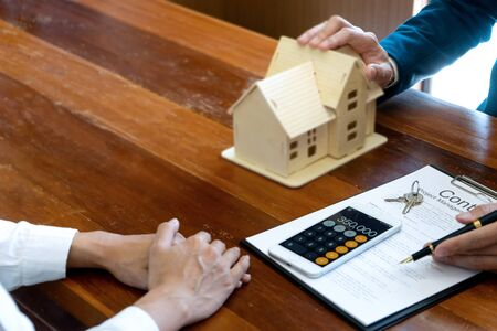 Business man agreement to sign for contract for new home buy or rent , talking and have a home model on the table Stock Photo - 124950357