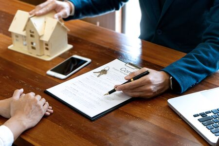 Business man agreement to sign for contract for new home buy or rent , talking and have a home model on the table Stock Photo - 124950750