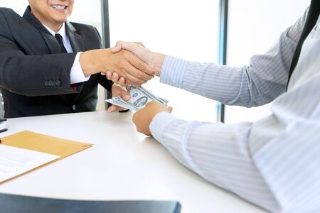Business man give bribe to the officer or another businessman money in their handshake, hand shake concept corruption money