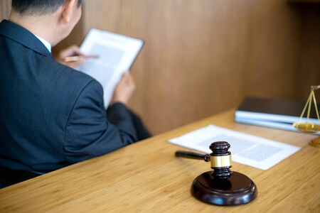 Businessman in suit or lawyer working with legal law documents. Judge gavel with Justice lawyers.  advice and justice law firm concept. 写真素材