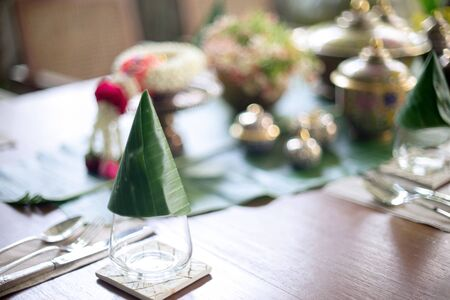 Prepare set on the table for Thai food ,silver ware and glass with banana leaf decorate