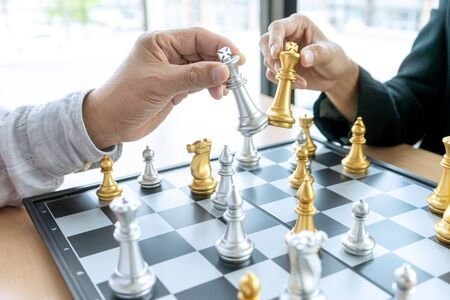 Businessman thinking and hold king chess on his hand,on board of chess game silver and gold color chess are on the table