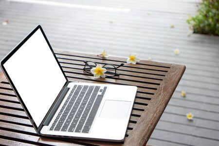 Laptop computer on the wood table near the swimming pool ,with white computer screen with clipping path