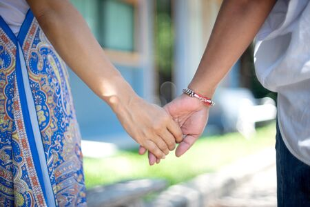 Woman and her friend hand together finger to hand ,friend hook each others little finger, walking together