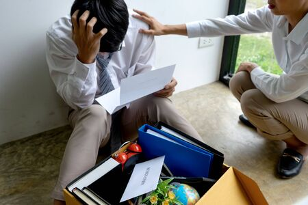 Young worker feel bad and sad, he receive resign note from his boss and company. Sad business man pack his belonging in the box and go back home. 写真素材