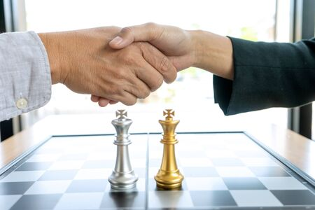 Businessman handshake near the chess board silver and gold color on the office desk.