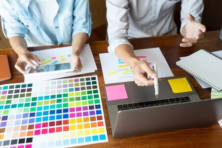Group of young designer working in the office to design a new product, use color chart and computer laptop for new smartphone design concept