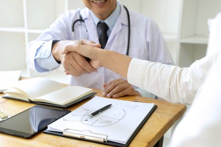 doctor handshake to the patient after they have good advice for the good health , bottle of medicine are on the table. 写真素材