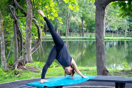 Woman more than 50 year old practicing yoga outdoor location near the lake in the park area. enjoy nice day in nature and positive energy 写真素材