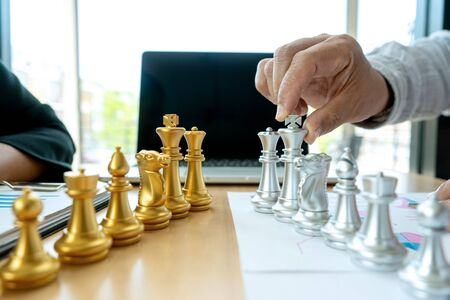 Businessman play chess on the marketing work place on office table for concept to win in strategy. 写真素材