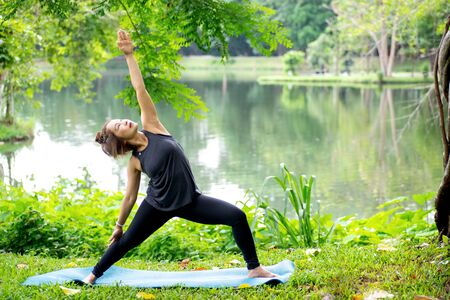 Woman more than 50 year old practicing yoga outdoor location near the lake in the park area. enjoy nice day in nature and positive energy 写真素材 - 129781534