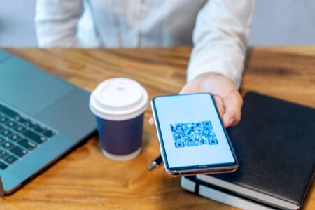 Lo smartphone funge da lettore di scanner per il codice. Un'attrezzatura per eseguire l'uso aziendale o ricevere i soldi online. Concetto di business non in contanti.