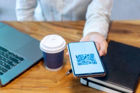 Smartfon służy jako czytnik skanera kodu. Sprzęt do prowadzenia działalności gospodarczej lub odbioru pieniędzy online. Koncepcja biznesowa bez gotówki.