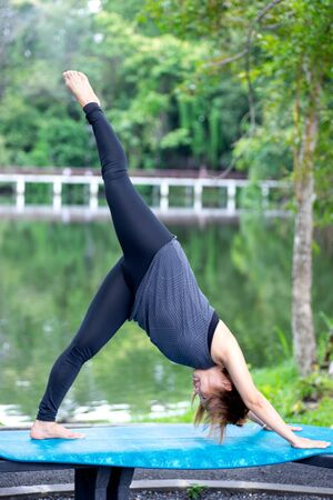 Woman more than 50 year old practicing yoga outdoor location near the lake in the park area. enjoy nice day in nature and positive energy 写真素材 - 129781191