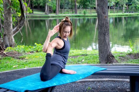 Woman more than 50 year old practicing yoga outdoor location near the lake in the park area. enjoy nice day in nature and positive energy 写真素材 - 129781224