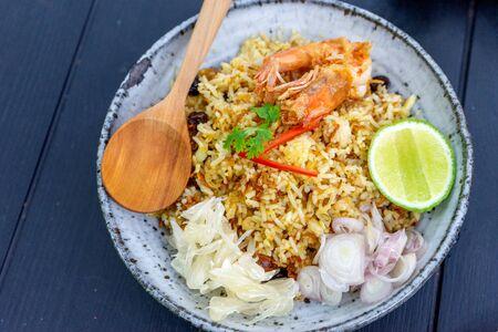Cuisine thaïlandaise riz frit aux crevettes dans un plat en bois sur une table en bois.