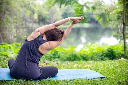 Woman more than 50 year old practicing yoga outdoor location near the lake in the park area. enjoy nice day in nature and positive energy 写真素材 - 129781012