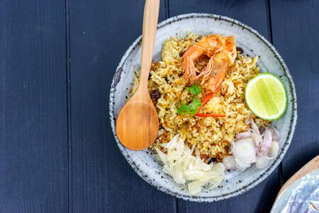 Thai food  fried rice whit shrimp in wood dish on wood table. Imagens