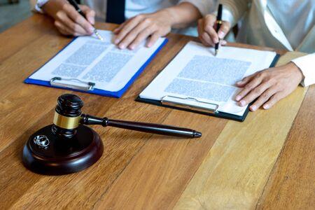 W kancelarii, mąż i żona podpisują dokument separacji prawnej, koncepcja prawnika prawa małżeńskiego. Zdjęcie Seryjne