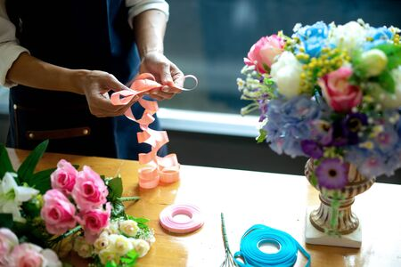 Image of flower artist woman working to decorate  artificial flowers decorate on the table with many  color of paper and plastic flower