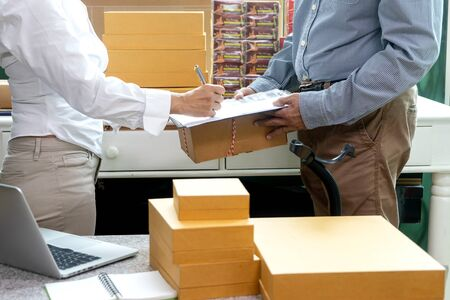 Small business woman Worker delivery service and working packing box, business owner working checking order to confirm before sending customer in post office, Shipment Online Sales with barcode scanner clipboard.