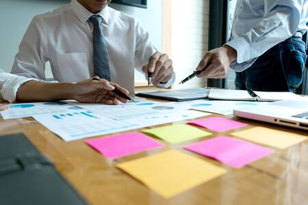 in the office Business meeting businessman and businesswoman work on the table have graph chart and color notepad  paper Imagens