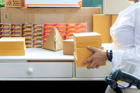 Small business woman Worker delivery service and working packing box, business owner working checking order to confirm before sending customer in post office, Shipment Online Sales with barcode scanner.