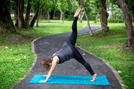 Woman more than 50 year old practicing yoga outdoor location  in the park area. enjoy nice day in nature and positive energy Imagens