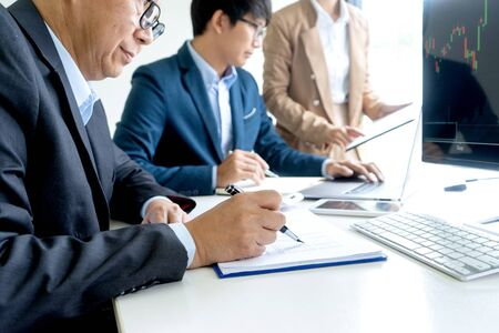 group of businessman  sit at the table looking at computer laptop in the office , they talking about stock market invest or talk with customer Imagens