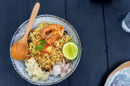 Thai food  Shrimp Fried Rice with wood spoon on wood table.