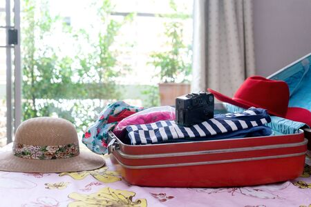 A woman packing the luggage prepare for her journey trip with a lot of her cloth, Imagens