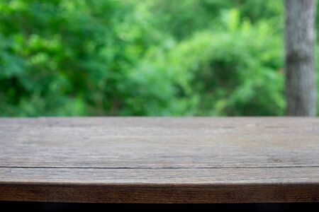 Brown Wooden board empty table texture table top on a green blur abstract background Bokeh green leaf