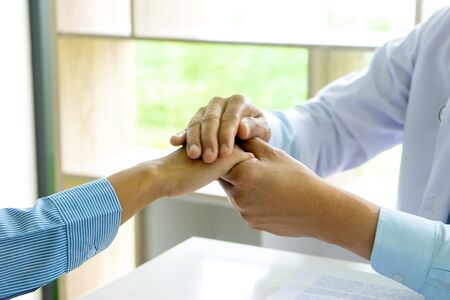 Doctor touch patient hand to give good thinking to them.