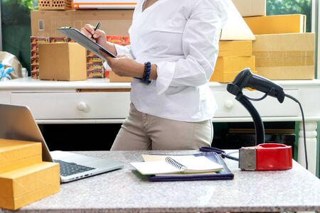 Small business woman Worker delivery service and working packing box, business owner working checking order to confirm before sending customer in post office, Shipment Online Sales 写真素材