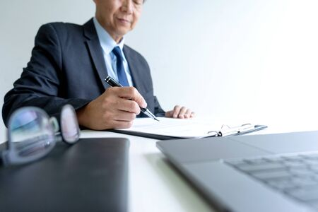 ceo or Elegant Businessman working  and sign paper or contact  on clipboard near laptop for analyzing data.