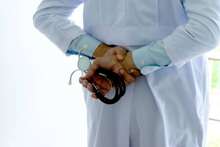 Back side of a doctor hold stethoscope in his hand