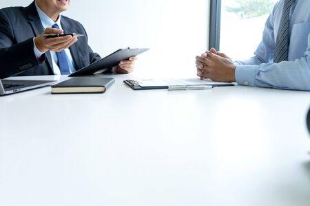 Gruppo di uomini d'affari in ufficio, giovani asiatici si siedono e parlano con curriculum mentre intervistano come candidato per un lavoro in una grande azienda. concetto di carriera e reclutamento Archivio Fotografico