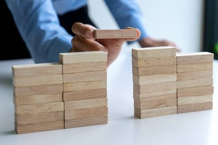 Young businessman try to build wall and tower from wooden brick block go to top of a tower 写真素材