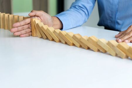 young business people use the hand to Stop wooden brick blog to stop loss