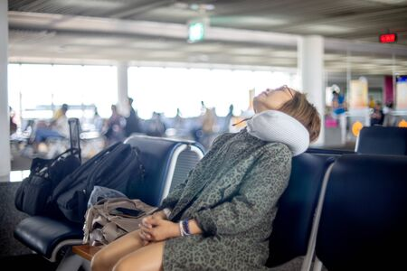woman Tourist relaxing and sleeping with neck pillow at airport terminal awaiting the delayed flight feel tired sleep on the chair in the airport.