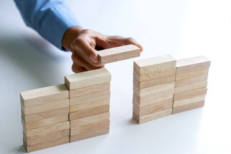 Young businessman try to build wall and tower from wooden brick block go to top of a tower